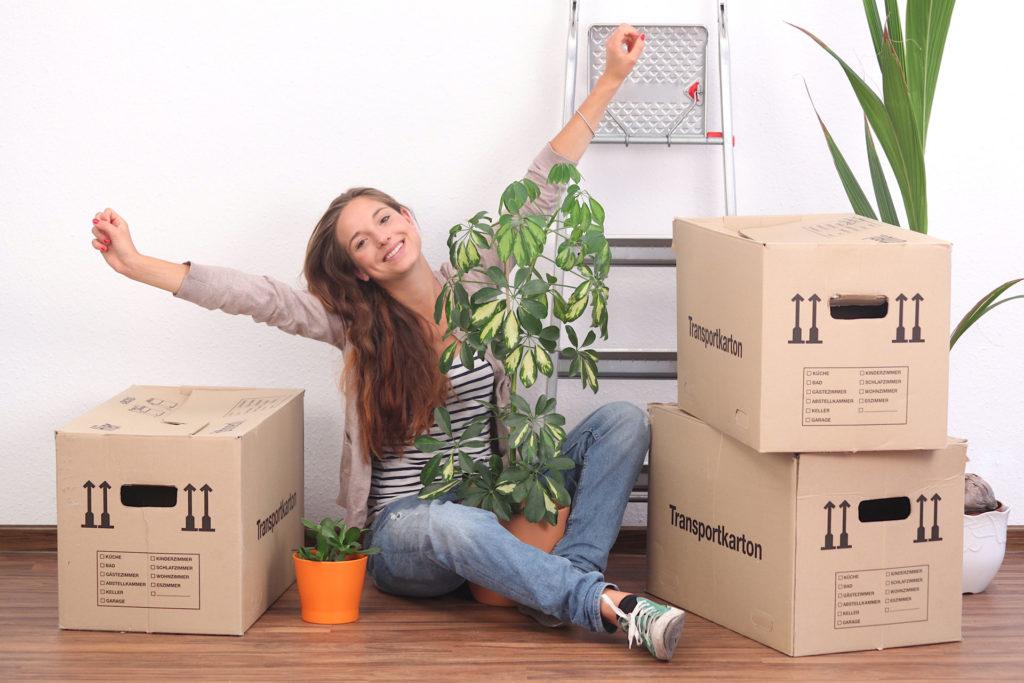 Frau in Wohnung mit gepackten Kartons - Lagerraum für Auslandsaufenthalt